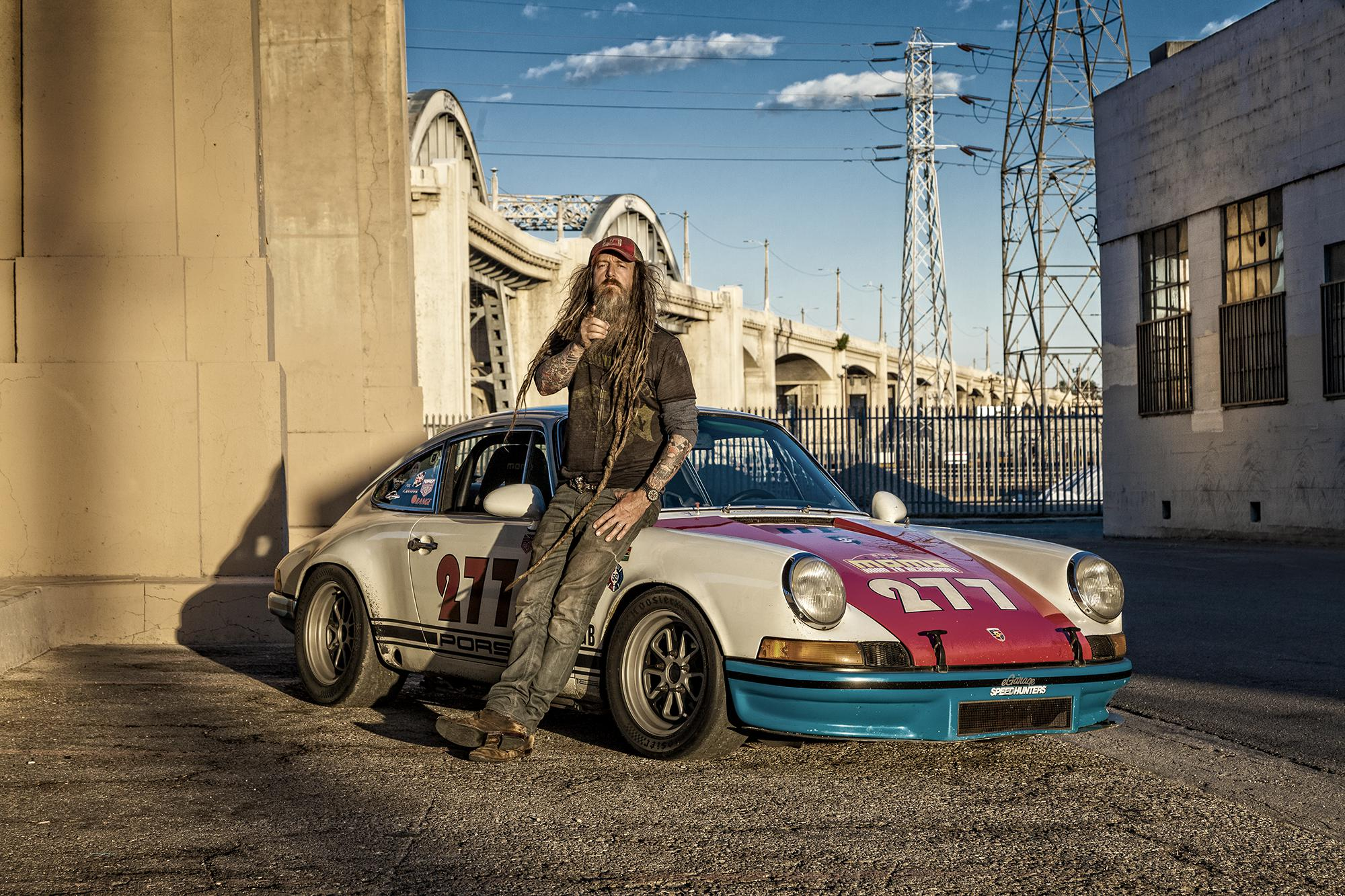 Magnus Walker leans against his 277 Porsche rac car under the 6th street bridge in Los Angeles