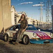 Magnus Walker leans against his 277 race car under the 6th street bridge in Los Angeles