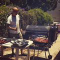Tattooed man attends to sausage cooking on a grill outdoors