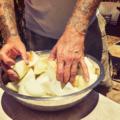 Tattooed man sorts through onions